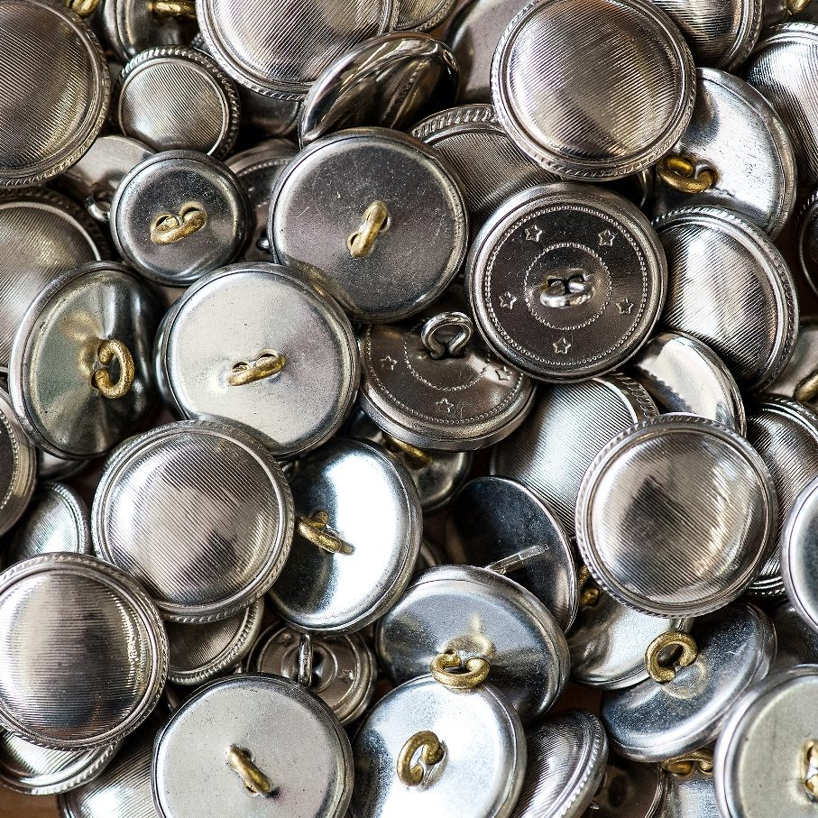 stock-photo-background-texture-of-a-pile-of-matched-round-silver-metal-buttons-for-making-garments-in-a-full-278915924